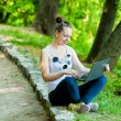 Happy woman with a laptop in outdoor — Stock Photo