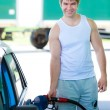 Man filling the car with gasoline in gas stations - Stock Photo