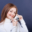 Beautiful girl with a photo camera on a dark blue background — Stock Photo