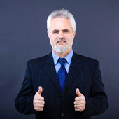 Studio shot of business man showing thumbs up sign on the dark — Stock Photo