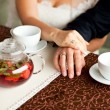 Man's and woman's hands on table in cafe. wedding rings — Stock Photo #29438675