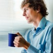 Man with a cup of tea in office — Stok fotoğraf