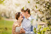 Portrait of young loving couple in flowering park — Stock Photo