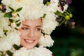 Beautiful young girl with a cap of flowers on her head — Stock Photo