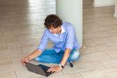 Kudrnaté mladík s notebookem sedí na podlaze — Stock fotografie