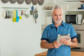 Old man with tablet sitting at the kitchen — Stock Photo