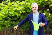 Portrait of senior man with watering can in garden — Stock Photo