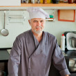 Friendly chef smiling on his kitchen — Stock Photo #46496565