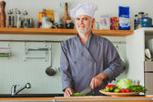 Friendly chef preparing vegetables in his kitchen — Stock Photo