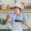 Friendly chef preparing  food in his kitchen and showing thumbs — Stock Photo #46533907