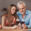 Grandfather with his granddaughter drinking wine in the kitchen — Stock Photo #47663397