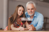 Young girl and senior man holding wine glasess — Stock Photo