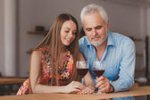 Grandfather with his granddaughter drinking wine  in the kitchen — Stock Photo