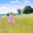 Little girl running in field — Stock Photo
