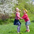 Little girls playing on a spring meadow — Stock Photo