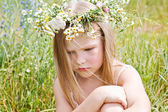 Resentful a little girl in a wreath of flowers — Stock Photo