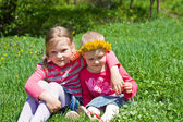 Little girls sitting in an embrace in the meadow — Stock Photo