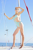 Graceful girl in blue swimsuit on sailboat — Stock Photo
