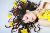 Portrait beautiful girl with long hair with narcissus — Stock Photo