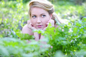 Beautiful girl in wood amongst green sheet — Stock Photo