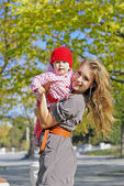 The young beautiful girl with the small child in autumn park — Stock Photo