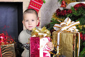 Boy near a Christmas tree with presents — Stock Photo