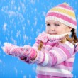 The little girl in a sweater and a hat with the snow — Stock Photo #17415943