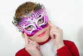 The young beautiful cheerful girl in a bright mask on a white ba — Stock Photo