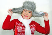 The young beautiful girl in a fur cap with a candle — Stock Photo