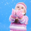 The little girl in a sweater and a hat with the snow — Stock Photo #17837351