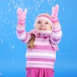 The little girl in a sweater and a hat with the snow — Stock Photo #17837359