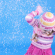 The little girl in a sweater and a hat with the snow — Stock Photo #17837389