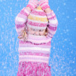 The little girl in a sweater and a hat with the snow - Stock Photo