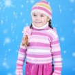 The little girl in a sweater and a hat with the snow — Stock Photo #17837497