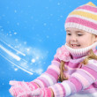 The little girl in a sweater and a hat with the snow — Stock Photo