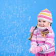 The little girl in a sweater and a hat with the snow — Stock Photo #17837505