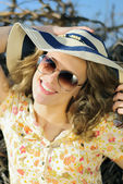 Beautiful girl in shorts and hat on grapevine — Stock Photo