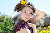 Beautiful girl in the yellow flowers — Stock Photo