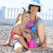 Little girl with her mother on the shore of the sea in the summe - Stock Photo
