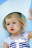 A little girl in large hat on the shore of the sea in the summer — Stock Photo