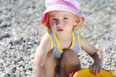 Little girl playing on the beach in the summer — Stock Photo