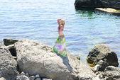 Beautiful girl on stone beside epidemic deathes — Stock Photo