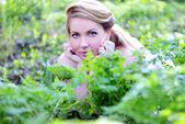 Vacker flicka i trä bland gröna blad — Stockfoto