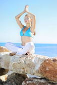 Graceful girl ashore epidemic deathes concerns with yoga — Stock Photo