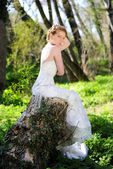 Beautiful girl bride in green wood by summer — Stock Photo