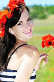 Beautiful girl with a wreath of poppies in a field — Stock Photo