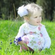 Little girl on a green meadow in a beautiful dress — Foto Stock