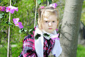 Little girl on green grass in the spring on a swing — Stock Photo