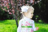 Little girl on a green meadow in a beautiful dress — Stock Photo