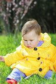 Liten flicka på en grön äng i en ljus gul jacka — Stockfoto